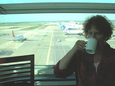 Carol sipping coffee in the President's Lounge at London's Gatwick Airport.