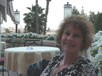 Carol on the balcony of the King David Hotel. The ancient wall of Old Jerusalem is in the background.