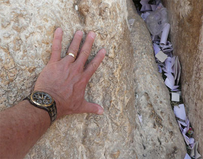 My hand on the stones of the Western Wall, near some prayers