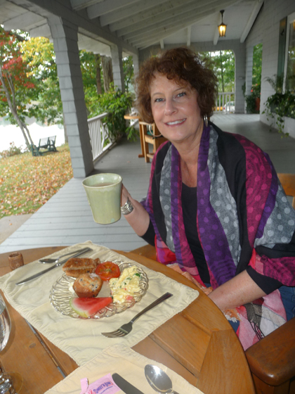 Carol enjoys a delicious breakfast, prepared by Aaron's father, of banana-orange smoothie, coffee, Greek eggs (spinach, feta, tomato) raisin toast and blueberry muffin, at the Buffelhead Cove B&B in Kennebunkport, Maine